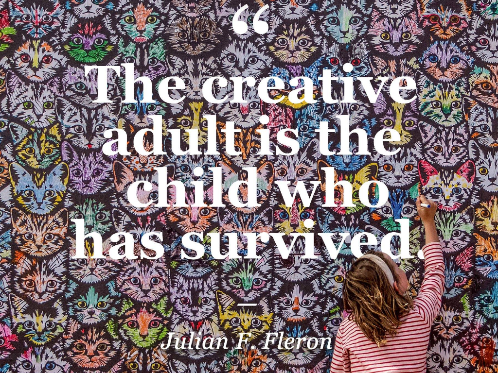 "Young white girl with blonde hair, viewed from behind colours in a mural of tabby cats, with the saying by Julian F. Fleron ""The creative adult is the child who has survived."""