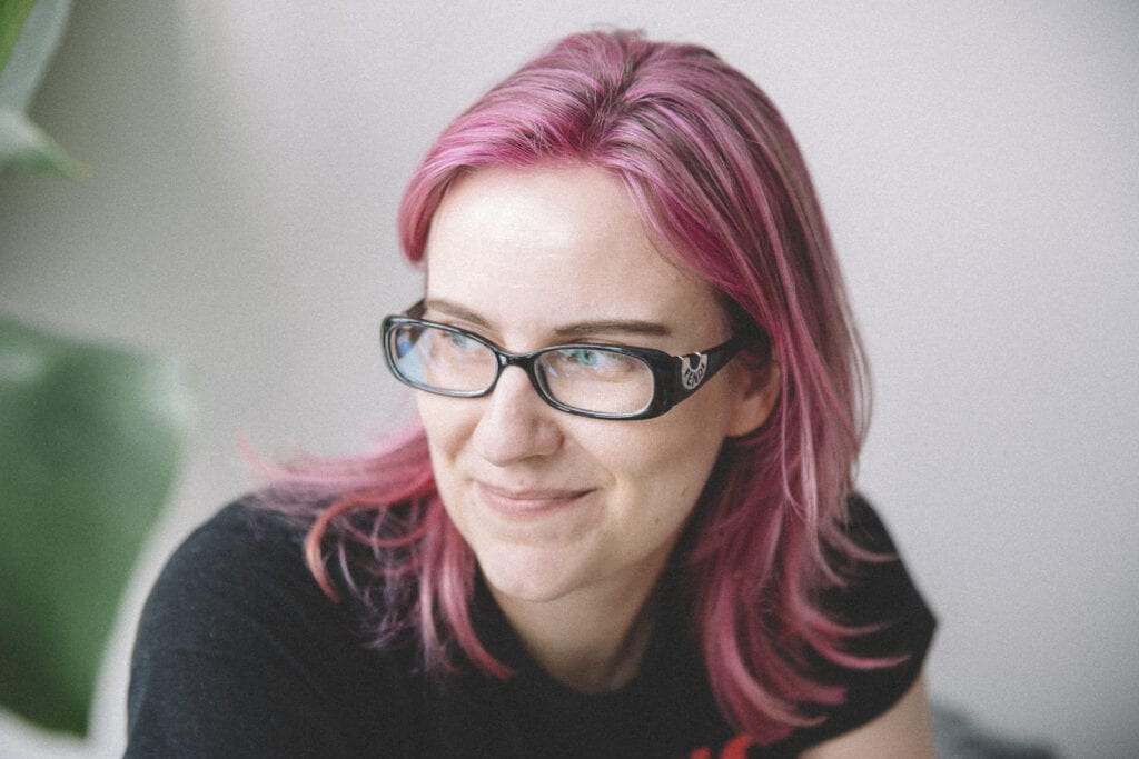 Photo of a 40-ish white woman with straight pink hair, looking away from the camera